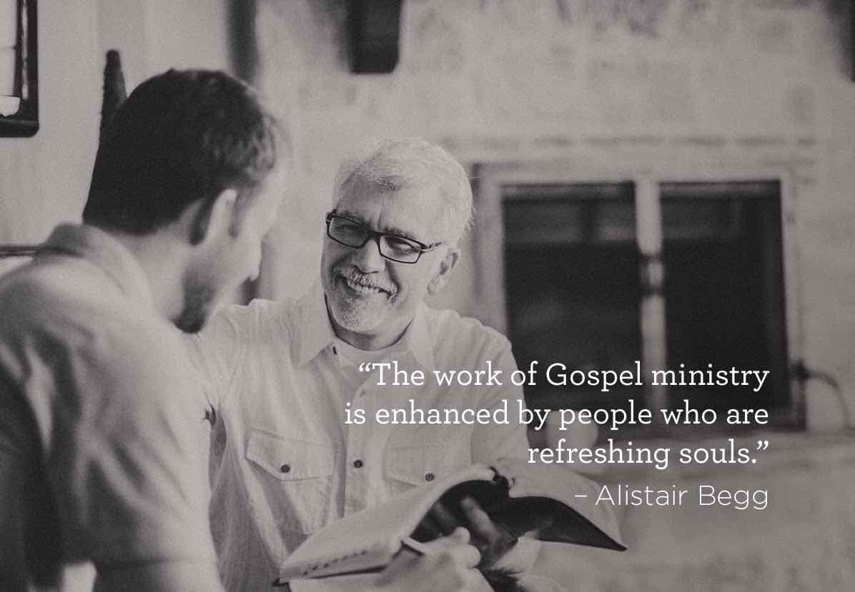 Photo of a pastor and another man smiling with an open Bible